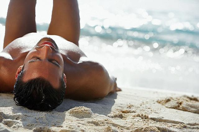 hombre tumbado en la arena de la playa